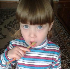 девочка чистит зубы для профилактики кариеса