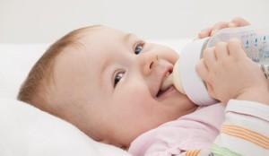 ребенок ест смесь из бутылочки