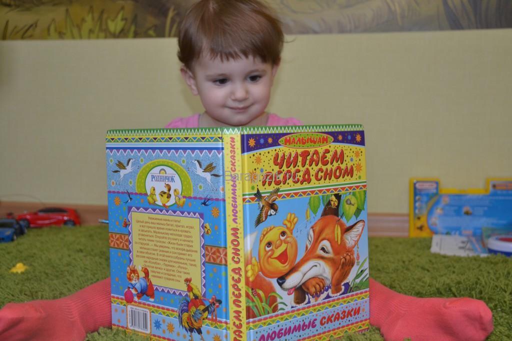 ребенок смотрит книжку со сказками